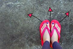 Directions de marche de flèches dessinées Usage de femme Flip Flop Red et position jaune sur le fond de ciment Photo libre de droits