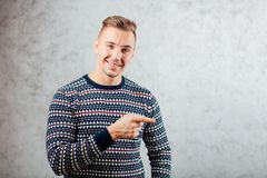 Directions de pointage de jeune homme sur le fond texturisé de mur en béton Images libres de droits