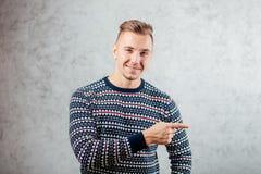Directions de pointage de jeune homme sur le fond texturisé de mur en béton Photographie stock libre de droits
