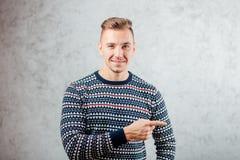 Directions de pointage de jeune homme sur le fond texturisé de mur en béton Photos libres de droits