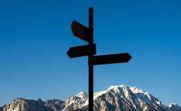 Directions où entrer en montagnes devant le ciel bleu Photos stock