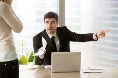 Directivo de la empresa enojado que despide al empleado incompetente que enciende f fotografía de archivo libre de regalías