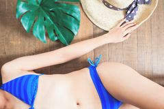 Directly above sexy woman in blue color bikini laying down on wo. Oden background, Summer holiday concept Royalty Free Stock Photo