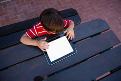 Directly above shot of boy using digital tablet while sitting at table Stock Photography