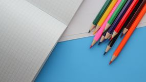 Directly Above Shot Of Colored Pencils By Books On blue background. Directly Above Shot Of Colored Pencils On blue background stock photography