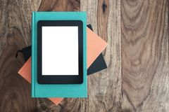 Top view of e-book reader on stack of books on wooden table royalty free stock photos