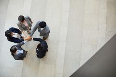 Business team stacking hands together. Directly above view of confident business team members in formalwear standing in circle in lobby and stacking hands royalty free stock photography