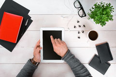 Directly above view of human hands with digital tablet. Digital tablet, diary, coffee cup and potted plant on work desk. Man working from home Stock Image