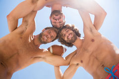 Directly below portrait of male friends huddling while playing American football
