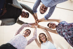 Directly below portrait of smiling business people raising hands together stock photo