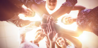 Directly below portrait of smiling business people stacking hands. Together at creative office Royalty Free Stock Photo