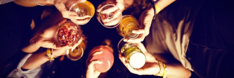 Directly below shot of friends holding drinks. While standing in nightclub Royalty Free Stock Image