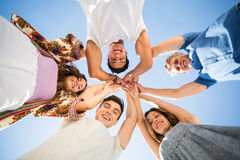 Directly below shot of friends huddling with arms raised Stock Photos
