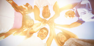 Directly below shot of friends huddling with arms raised Stock Photo