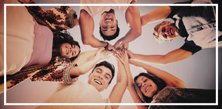 Directly below shot of friends huddling with arms raised. Against sky on sunny day Stock Images