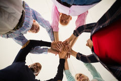 Directly below shot of happy senior friends stacking hands. While standing in art class royalty free stock image