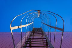 Directly below shot of metallic ladder on wall against sky. Directly below shot of metallic ladder on wall against the sky royalty free stock photos