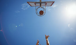 Directly below shot of person playing basketball. Against sky on sunny day royalty free stock photography