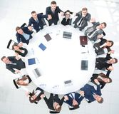 Director and business team sitting at the round table and holding each other`s hands. royalty free stock photography