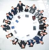Director and business team sitting at the round table and holding each other`s hands. Royalty Free Stock Photo