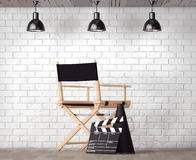 Director Chair, Movie Clapper and Megaphone in front of Brick Wa. Ll with Blank Frame extreme closeup Royalty Free Stock Photo