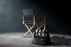 Director Chair, Movie Clapper and Megaphone in the volumetric li. Ght on a black background. 3d Rendering Royalty Free Stock Photos