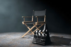 Director Chair, Movie Clapper and Megaphone in the volumetric li. Ght on a black background. 3d Rendering stock illustration