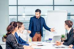 Director of company having business meeting with his staff. Showing presentation on flipchart or magnetic desk Stock Image