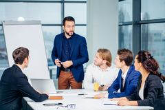 Director of company having business meeting with his staff. Showing presentation on flipchart or magnetic desk Royalty Free Stock Image