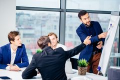 Director of company having business meeting with his staff. Showing presentation on flipchart or magnetic desk Stock Photo