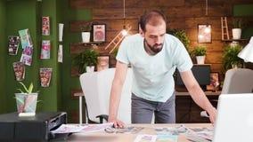 Director de arte caucásico en su oficina que intenta elegir el mejor diseño para su proyecto siguiente metrajes