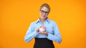 Director de banco de sexo femenino que lleva a cabo el piggybank a disposición, fondo de jubilación, seguro de depósito almacen de metraje de vídeo