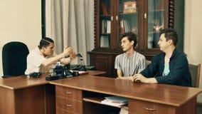 Director de cine en hablar enojado de la camisa blanca con los trabajadores de la oficina sobre el guión metrajes