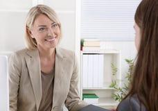 Director de gerente de sexo femenino en una entrevista de trabajo con una mujer joven fotos de archivo