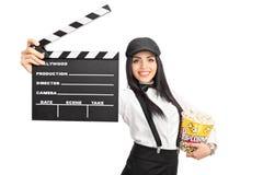 Director de película de sexo femenino que sostiene un clapperboard y palomitas Imagen de archivo