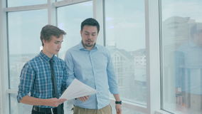 Director discuss project with employee, gives advice, using digital tablet in new modern office. HD stock footage