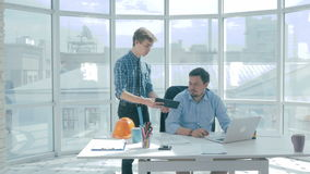 Director discuss project with employee, gives advice, using digital tablet in new modern office. stock video footage