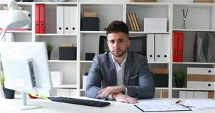 Director en la chaqueta gris que se sienta en la tabla en la oficina blanca y que sacude la cabeza negativamente