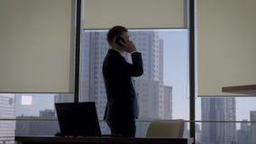 Director en un traje de negocios que habla en el teléfono en la ventana de la oficina cercana con el lugar de trabajo metrajes