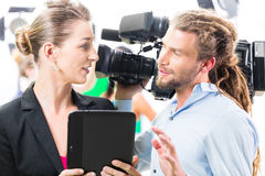Director giving cameraman direction for video production. Team discussion or Director giving cameraman scene direction on set of a video production for TV or Royalty Free Stock Photo