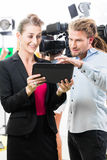 Director giving cameraman direction for video production. Team discussion or Director giving cameraman scene direction on set of a video production for TV or royalty free stock photography