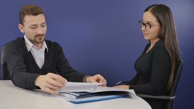 The director looks through a resume of new worker on job interview. Executive director sits in armchair in the office and has a conversation with a young woman stock video