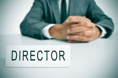 Director. A man in suit sitting in a desk with a nameplate in front of him with the word director written in it stock photo