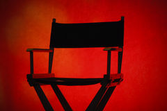 Director's Chair. Silhouette of a traditional wood and canvas Director's Chair on a red background - Horizontal stock images
