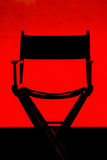 Director's Chair silhouette on Red Stage. Silhouette of a single traditional wood and canvas Director's Chair on a red stage background stock image