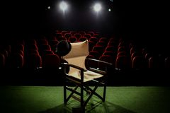 Director& x27;s chair on stage. In front of empty seats and in between curtains royalty free stock images