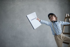 Director with a screenplay. Boy with a screenplay on stairs Stock Photo