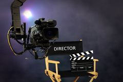 Director seat on set with video camera. With bright spotlight in background stock photography