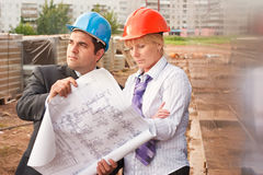 Director with subordinate on construction site. Director and engineer on construction site of shopping center Royalty Free Stock Images
