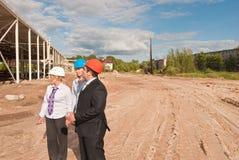 Director with subordinates on construction site. Director and engineers on construction site of shopping center Stock Photos